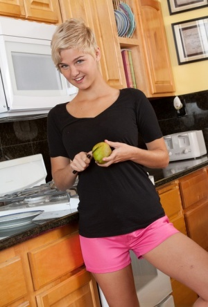 Short haired girl eats an apple while stripping to her socks in the kitchen
