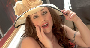 Clothed female Eva Notty shows off her pretty face in a sunhat