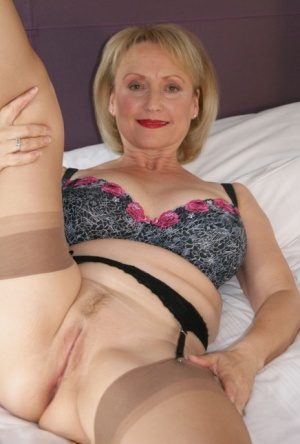 Sexy mature woman shows her big tits and landing strip pussy in retro nylons