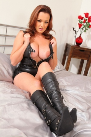 Redhead model Jodie Gasson works clear of a latex dress in calf high boots